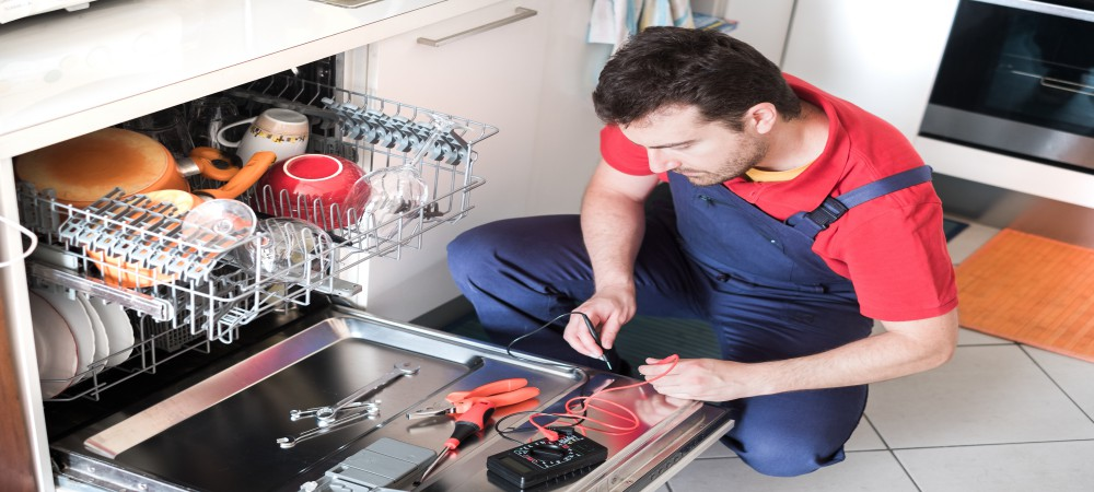Professional worker repairing the dishwasher in the kitchen